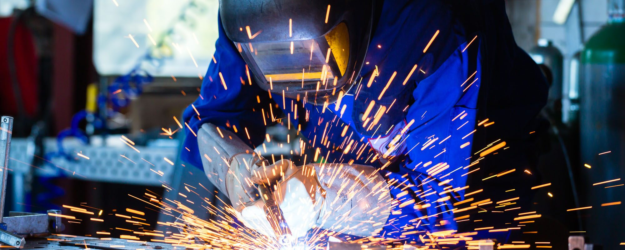 Welder bonding metal with welding device in workshop, lots of sparks to be seen, he wears welding goggles